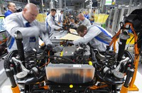 In this Tuesday, Feb. 25, 2020 file photo, workers complete an electric car ID.3 body at the assembly line during a press tour at the plant of the German manufacturer Volkswagen AG (VW) in Zwickau, Germany. (AP Photo/Jens Meyer)