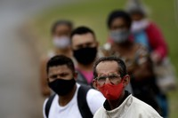 People wear masks against the spread of the new coronavirus, at a bus stop in Valparaiso, Brazil, on May 20, 2020. (AP Photo/Eraldo Peres)