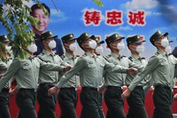 Chinese People's Liberation Army (PLA) soldiers wearing face masks to protect against the spread of the new coronavirus march past a banner depicting Chinese President Xi Jinping at their living squatter inside the Tiananmen Gate in Beijing during a plenary session of China's National People's Congress (NPC) at the Great Hall of the People in Beijing,on May 25, 2020. (AP Photo/Andy Wong)