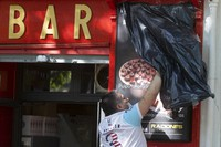 A worker uncovers the front of a bar ready to open for the first time in over two months in Madrid, Spain, on May 25, 2020. Spain is making progress on its staggered plan out of the confinement against the coronavirus. (AP Photo/Paul White)