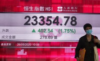A woman wearing face mask walks past a bank electronic board showing the Hong Kong share index at Hong Kong Stock Exchange on May 26, 2020. (AP Photo/Vincent Yu)