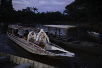 Funeral workers transport a coffin by boat carrying the body of an 86-year-old woman who lived by the Negro River and is suspected to have died of COVID-19, near Manaus, Brazil, on May 14, 2020. (AP Photo/Felipe Dana)