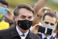 Brazil's President Jair Bolsonaro wearing a face mask stands amid supporters taking pictures with cell phones as he leaves his official residence of Alvorada palace in Brasilia, Brazil, on May 25, 2020. (AP Photo/Eraldo Peres)