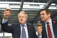In this file photo dated Nov. 7, 2019, showing Britain's Prime Minister Boris Johnson alongside Douglas Ross, parliamentary under-secretary of state for Scotland, right in Moray, Scotland. (Stefan Rousseau / PA via AP)