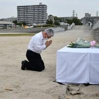 砂浜陥没事故の現場で手を合わせる泉房穂市長=兵庫県明石市大蔵海岸通1で、浜本年弘撮影