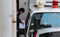 Shinji Aoba, the suspect in the deadly arson attack last July on a Kyoto Animation Co. studio, is seen getting carried on a stretcher into Kyoto Prefectural Police's Fushimi Police Station in Kyoto's Fushimi Ward on May 27, 2020. (Mainichi/Yohei Koide)
