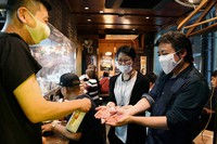 People receive alcohol spray as they enter a restaurant in Tokyo's Shinjuku Ward on the evening of May 26, 2020. A clear plastic sheet has been installed between the cooking area and the counter where customers sit. (Mainichi/Kimi Takeuchi)
