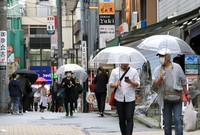 People are seen walking with umbrellas on a road in the Tokyo suburb of Musashino that leads to Inokashira Park on May 26, 2020. (Mainichi/Naotsune Umemura)