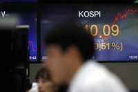 Currency traders watch computer monitors near the screen showing the Korea Composite Stock Price Index (KOSPI) at the foreign exchange dealing room in Seoul, South Korea, on May 27, 2020.(AP Photo/Lee Jin-man)