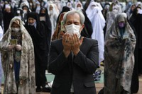 Worshippers wearing protective face masks offer Eid al-Fitr prayers outside a mosque to help prevent the spread of the coronavirus, in Tehran, Iran, on May 24, 2020. (AP Photo/Vahid Salemi)