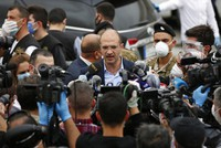 In this April 5, 2020, Lebanese Health Minister Hamad Hassan, center, ignoring social distancing rules and not wearing a mask, speaks with journalists during the arrival of Lebanese passengers who were stuck in Saudi Arabia and other countries because of the coronavirus outbreak, outside Rafik Hariri Airport, in Beirut. (AP Photo/Hussein Malla)