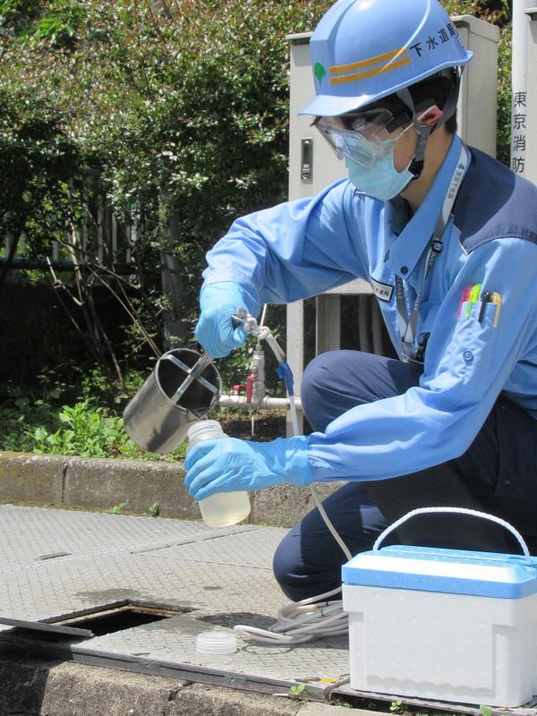 処理済みの下水を採取する都下水道局の職員
