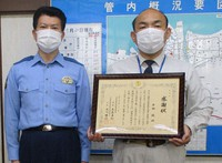 Makoto Hirata, right, who holds a certificate of appreciation he received for helping an elderly woman avoid being scammed, and Masanori Tachibana, chief of Niihama Police Station, are seen in this May 21, 2020 photo provided by the police station.