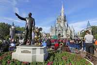 In this Jan. 9, 2019 photo, guests watch a show near a statue of Walt Disney and Micky Mouse in front of the Cinderella Castle at the Magic Kingdom at Walt Disney World in Lake Buena Vista, part of the Orlando area in Fla.  (AP Photo/John Raoux)