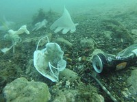 This photo taken on May 21, 2020 and provided by environmental group Operation Mer Propre (Operation Clean Sea) shows plastic gloves, face masks and other waste off Antibes, southern France. (Operation Mer Propre via AP)