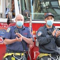 病院の前で拍手を送るニューヨーク市消防の消防士=米ニューヨークで2020年5月25日、隅俊之撮影
