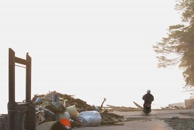愛車にまたがり必死に妻を捜し続ける男性=岩手県陸前高田市広田町で2011年6月4日午前4時57分、石井諭撮影