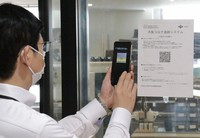 An Osaka Prefectural Government employee demonstrates how to register an email with a system to send alerts to users if someone who has been to the same facility on the same day tests positive for the coronavirus, at the prefectural headquarters in Osaka's Chuo Ward, on May 29, 2020. (Mainichi/Hirokage Tabata)