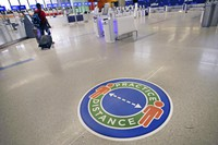 A traveler passes a sign recommending practicing social distancing, to limit spread of the coronavirus outbreak, at the nearly passenger-less JetBlue terminal at Logan Airport in Boston, on May 29, 2020. (AP Photo/Charles Krupa)