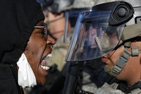 Protesters and National Guardsmen face off on East Lake Street, on May 29, 2020, in St. Paul, Minn. (AP Photo/John Minchillo)