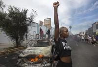 A protester poses for photos next to a burning police vehicle in Los Angeles, on May 30, 2020, during a demonstration over the death of George Floyd. (AP Photo/Ringo H.W. Chiu)