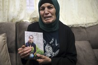 Rana, mother of Iyad Halak, 32, holds his photo at their home in East Jerusalem's Wadi Joz, on May 30, 2020. (AP Photo/Mahmoud Illean)