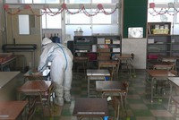 A worker disinfects a classroom at Moritsune Elementary School in Kitakyushu's Kokuraminami Ward on May 29, 2020, after a student tested positive for the novel coronavirus. (Image partially modified) (Mainichi/Noriko Tokuno)