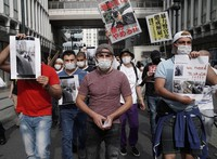 A Kurdish man, center, who suffered neck injuries that took one month to heal after he was restrained by two police officers on a street in Tokyo's Shibuya district, marches with his supporters to protest against police violence in Shibuya Ward on May 30, 2020. (Mainichi/Yoshiya Goto)