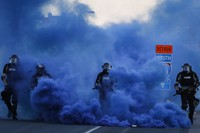 Police in riot gear walk through a cloud of blue smoke as they advance on protesters near the Minneapolis 5th Precinct, on May 30, 2020, in Minneapolis. (AP Photo/John Minchillo)