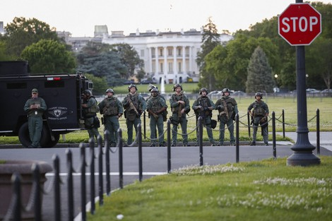 Law enforcement officers from Calvert County Maryland Sheriff's Office stand on the Ellipse, area just south of the White House in Washington, as they watch demonstrators protest the death of George Floyd, on May 31, 2020. (AP Photo/Alex Brandon)
