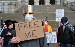 5月初旬には全米各地で経済再開を求めるデモが……(「私を自由の身にしろ」と書いたプラカードを掲げるデモ参加者)=米ニューヨーク州オールバニで2020年5月1日、隅俊之撮影