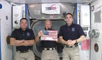 In this image taken from NASA video on June 1, 2020, NASA astronauts Robert L. Behnken, left, and Chris Cassidy, right, listen as commander Douglas Hurley speaks about retrieving the American flag left behind at the International Space Station nearly a decade ago. (NASA via AP)