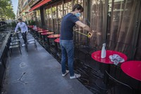 Pierre-Antoine Boureau handling a tape measure as he prepares the terrace of a restaurant in order to respect distancing to help curb the spread of the coronavirus in Paris, on June 1, 2020. (AP Photo/Michel Euler)