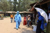 In this April 15, 2020 file photo, a health worker from an aid organization walks wearing a hazmat suit at the Kutupalong Rohingya refugee camp in Cox's Bazar, Bangladesh. (AP Photo/Shafiqur Rahman)