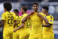 Achraf Hakimi Mouh of Borussia Dortmund celebrates scoring his teams fourth goal of the game with a 'Justice for George Floyd' shirt during the German Bundesliga soccer match between SC Paderborn 07 and Borussia Dortmund at Benteler Arena in Paderborn, Germany, on May 31, 2020. (Lars Baron/Pool via AP)