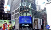 This image from video made available by NASA shows a live video of astronaut Chris Cassidy, right, ringing the opening bell of the Nasdaq Stock Exchange from the International Space Station, accompanied by fellow astronauts Robert L. Behnken, left, and Doug Hurley, broadcast on the exterior of the Nasdaq building on June 2, 2020, in New York. (NASA via AP)