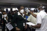 In this March 4, 2020 file photo, a Nigerian port health official, right, uses a thermometer to screen an Ethiopian Airline cabin crew for the coronavirus, upon arrival at the Murtala Muhammed International Airport in Lagos, Nigeria. (AP Photo/Sunday Alamba)