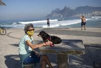 Lucia and her dog Jujuba sit at Arpoador beach, amid the new coronavirus pandemic in Rio de Janeiro, Brazil, on June 2, 2020. (AP Photo/Silvia Izquierdo)