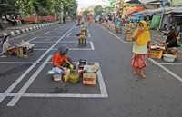 Vendors sit on marked positions to maintain physical distancing in an attempt to curb the spread of the new coronavirus outbreak at a traditional market in Surabaya, East Java, Indonesia, on June 3, 2020. (AP Photo/Trisnadi)