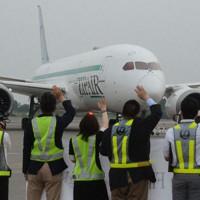 出発する初便に手を振って見送る「ZIPAIR Tokyo」と日本航空の社員ら=成田空港で