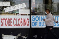 In this May 21, 2020 photo, a man looks at signs of a closed store due to COVID-19 in Niles, Illinois. (AP Photo/Nam Y. Huh)
