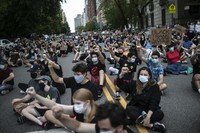 Protesters sit together with their fists in the air during a solidarity rally calling for justice over the death of George Floyd on June 3, 2020, in New York. (AP Photo/Wong Maye-E)
