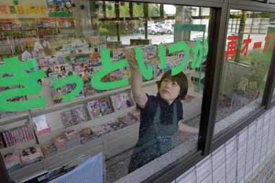 飯舘村で唯一の書店が閉店し、「きっといつか再オープン」の文字を窓に張る副店長=福島県飯舘村で2011年6月15日午後6時15分、竹内幹撮影