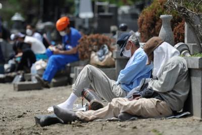道路側溝のヘドロの掃除をし、昼休みに眠るボランティアの男性=宮城県石巻市で2011年6月16日午後0時33分、丸山博撮影