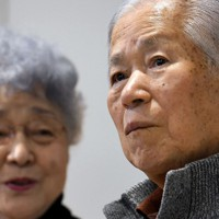 「横田夫妻を囲む会」で、スクリーンに映し出された娘のめぐみさんの写真を見て涙をこらえる横田滋さん(右)。左は妻の早紀江さん=川崎市で2017年2月5日、竹内紀臣撮影