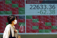 A woman walks past an electronic stock board showing Japan's Nikkei 225 index at a securities firm in Tokyo on June 5, 2020. Asian markets are mostly lower after Wall Street rally takes a breather, as investors parse unemployment data. (AP Photo/Eugene Hoshiko)