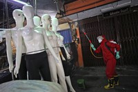 A fireman sprays disinfectant at mannequins as a precaution against the coronavirus outbreak, at Tanah Abang textile market in Jakarta, Indonesia, on June 4, 2020. (AP Photo/Dita Alangkara)