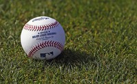 In this Feb. 17, 2017 file photo, a baseball is seen on the grass at the Cincinnati Reds baseball spring training facility in Goodyear, Arizona. (AP Photo/Ross D. Franklin)