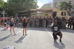 米ホワイトハウスの近くで道路を封鎖するために若者らの前に立ちはだかる警察官や州兵=6月3日、古本陽荘撮影