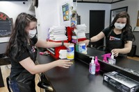Stylist Kayla Addink arranges items in her workspace on June 4, 2020, as she prepares for her first day back on the job at the West View Barber Shop when most of southwest Pennsylvania loosens COVID-19 restrictions, in West View, Pennsylvania. (AP Photo/Keith Srakocic)